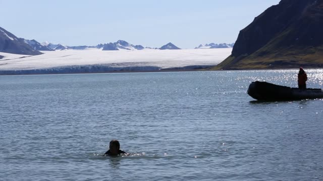 a woman takes a dip in the arctic ocean in northern svalbard in front of a glacier - arctic stock videos & royalty-free footage