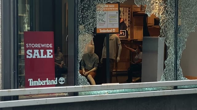 woman takes a photo of a window shattered at a timberland store along michigan avenue after it was looted on august 10, 2020 in chicago, illinois.... - other stock videos & royalty-free footage