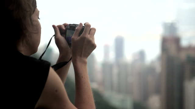 A woman takes a photo of buildings in the region of Hong Kong.