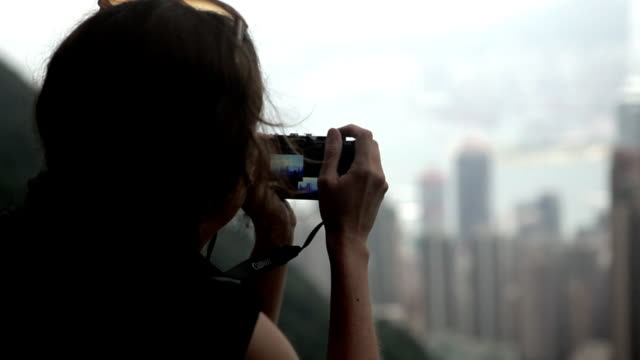 A woman takes a photo of the buildings in Hong Kong.