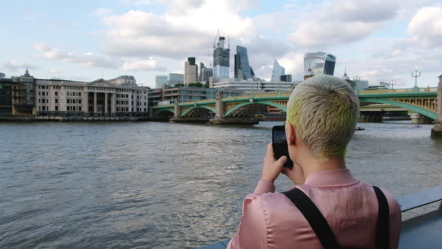 woman takes a photo of the london cityscape along the thames river in london, england at sunset. - naga river stock videos and b-roll footage