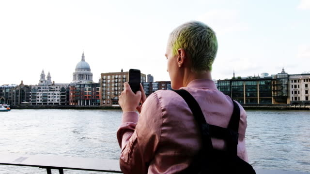 Woman takes a photo of the London cityscape along the Thames River in London, England at sunset.