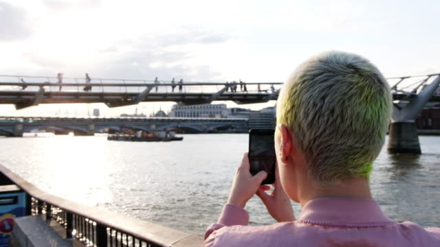 woman takes a photo of the millennium bridge along the thames river in london, england at sunset. - naga river stock videos and b-roll footage