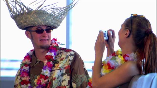 a woman takes a picture of her husband wearing a lei and straw hat while waiting at the airport gate. - straw hat stock videos & royalty-free footage