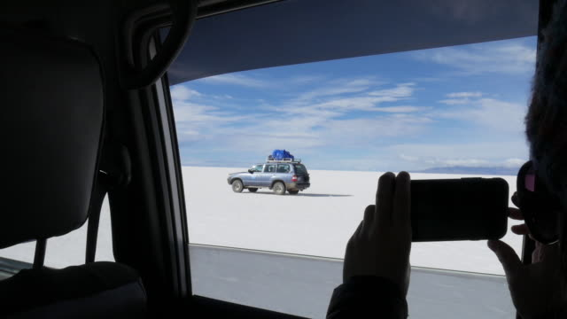 A woman takes a picture to a car in Uyuni Salar