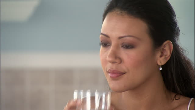 a woman takes a vitamin with a glass of water. - vitamin stock videos & royalty-free footage