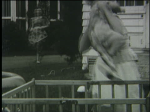 b/w 1951 woman takes baby from playpen rushes away outdoors during air raid - 1951 stock videos & royalty-free footage