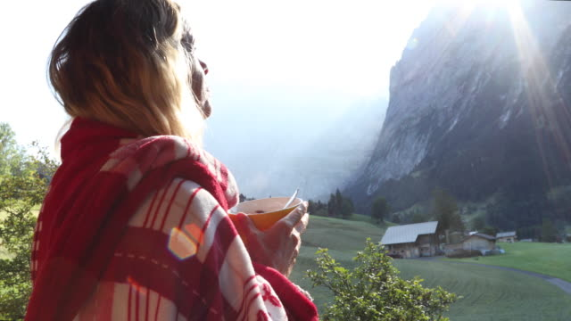 Woman takes bowl of muesli onto deck, below mountains