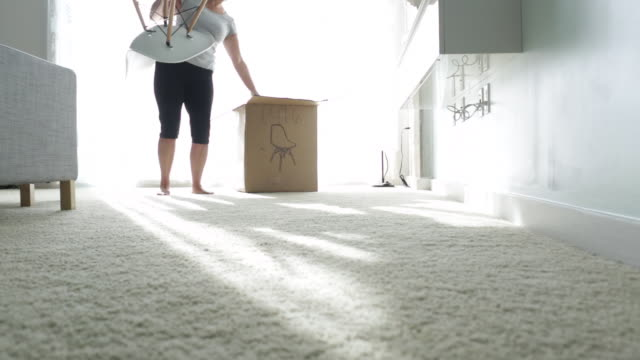 ls woman takes chair out of box and uses tools to assemble. - 片付いた部屋点の映像素材/bロール