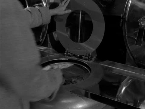 woman takes her washing out of a spinning machine at a launderette. - waschsalon stock-videos und b-roll-filmmaterial