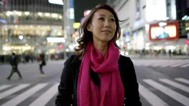 MS A woman takes in the sight of Shibuya Crossing / Tokyo, Japan