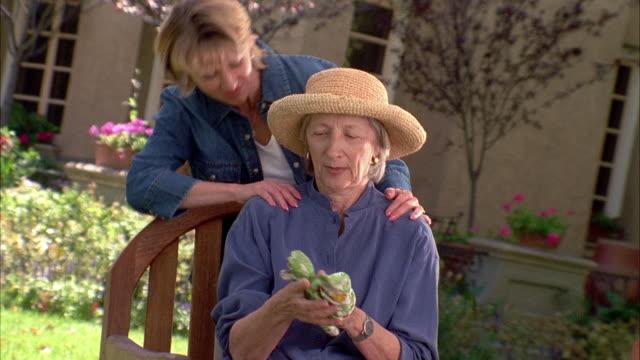 a woman takes off her gardening gloves then her daughter comes to hug her. - trädgårdshandske bildbanksvideor och videomaterial från bakom kulisserna