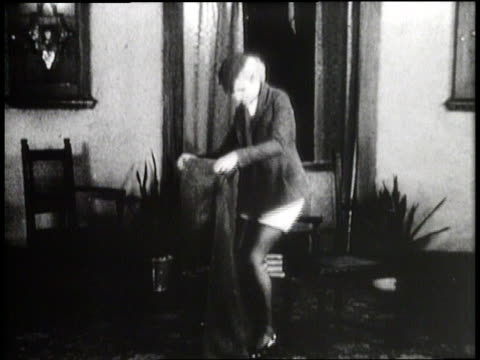 a woman takes off her skirt and puts on a pair of pants - pantaloni video stock e b–roll