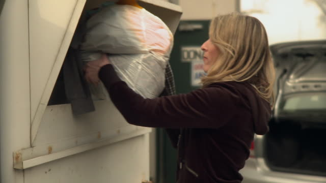 ms r/f woman takes out clothes out of car and puts in donation bin / morris, illinois, usa - 服装点の映像素材/bロール