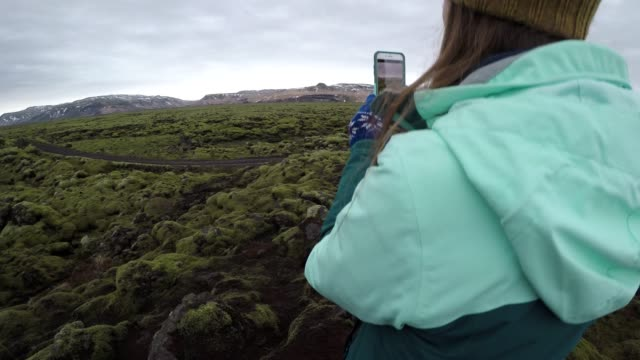 woman takes phone photo of moss-covered lava field - accessibility stock videos & royalty-free footage