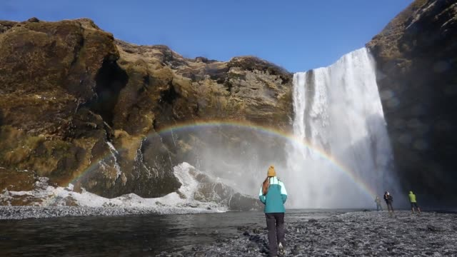 Woman takes phone picture of waterfall and rainbow