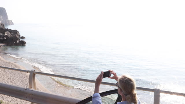 woman takes photo from car door, coastline road - see other clips from this shoot 56 stock videos & royalty-free footage