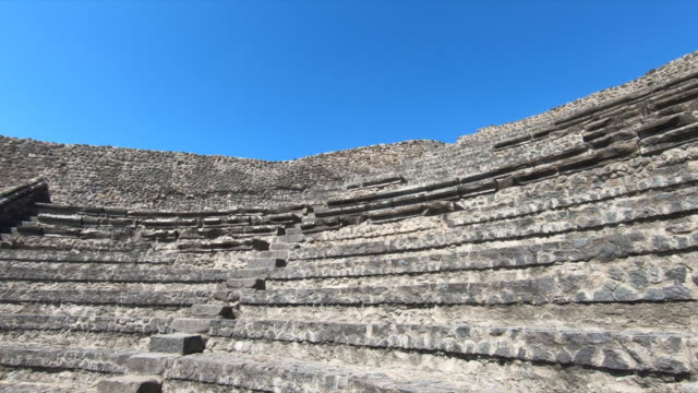 a woman takes photos in a theater in the ancient ruins sightseeing historic landmark of pompeii, italy, europe. - slow motion - amphitheatre stock videos & royalty-free footage