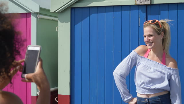 woman takes photos of friend posing against beach hut. - 英格蘭 個影片檔及 b 捲影像