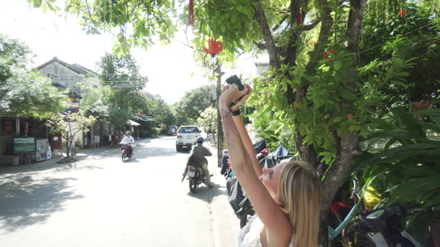 Woman takes photos of lantern hanging from tree