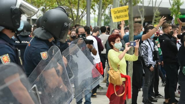 woman takes photos of the crowds chanting slogans as police line up watching the event during a demonstration, in the vallecas neighborhood, against... - number 2 stock videos & royalty-free footage