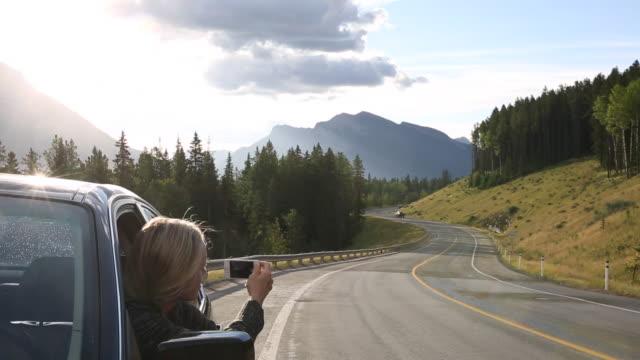 vídeos de stock e filmes b-roll de woman takes pic from car window, mountain road - só uma mulher madura