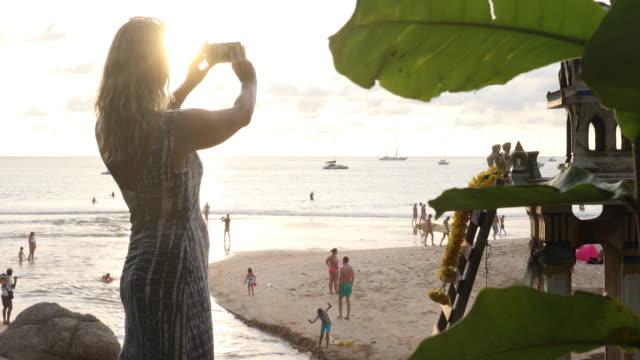 woman takes pic near shrine as sun sets over beach - meraviglie della natura video stock e b–roll