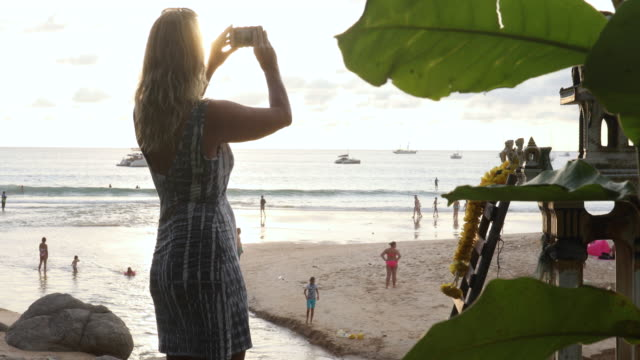 woman takes pic near shrine as sun sets over beach - photography themes stock videos & royalty-free footage