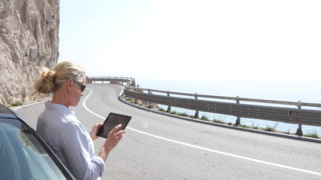Woman takes pic with digital tablet beside car, above sea