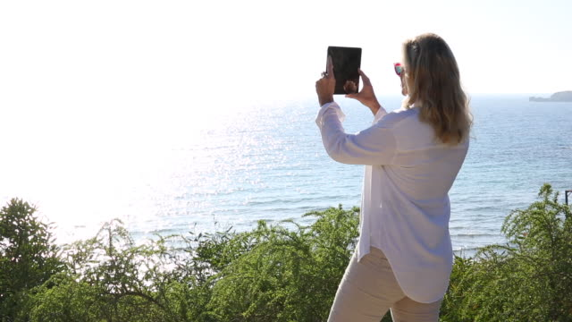 Woman takes pic with digital tablet, looks towards camera
