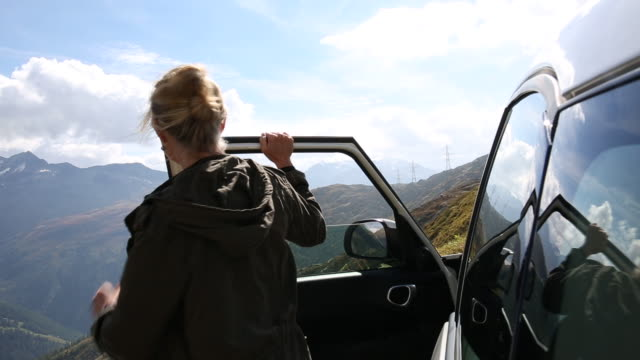 Woman takes picture with smart phone, on mountain pass