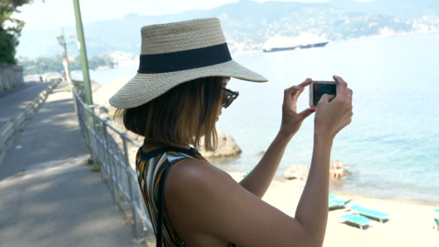 vídeos de stock, filmes e b-roll de a woman takes pictures with her mobile device phone at a beach resort in a luxury resort town in italy, europe. - slow motion - artigo de vestuário para cabeça