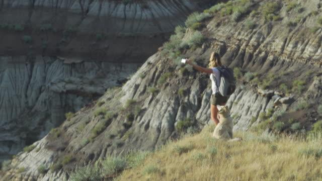 stockvideo's en b-roll-footage met vrouw neemt selfie op uitzichtpunt canyon met hond - alleen één mid volwassen vrouw