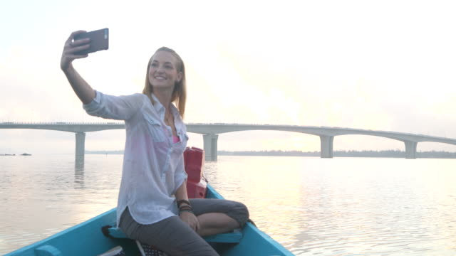 Woman takes selfie on boat at sunset