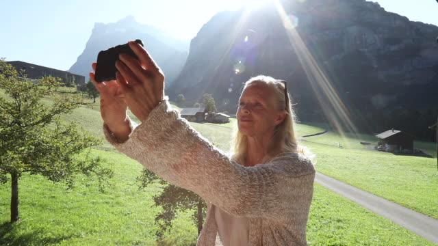 vídeos de stock e filmes b-roll de woman takes selfie pic on deck, below mountains - mulheres maduras