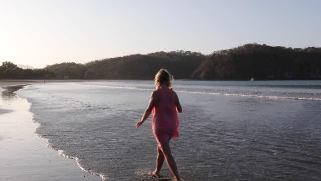 vidéos et rushes de la femme prend la photo de selfie tout en marchant le long de la plage, au lever du soleil - 60 64 ans