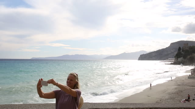 Woman takes selfie whie pushing bicycle, looks out to sea