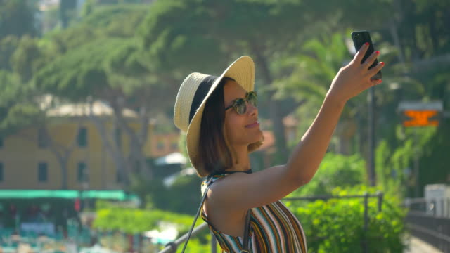 vídeos de stock, filmes e b-roll de a woman takes selfies and uses facetime video calling in a luxury resort town in italy, europe. - slow motion - celular com câmera