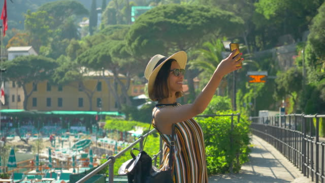 vídeos de stock e filmes b-roll de a woman takes selfies and uses facetime video calling in a luxury resort town in italy, europe. - slow motion - tourist