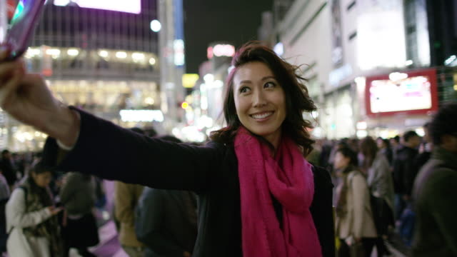 MS A woman takes selfies at Shibuya crossing / Tokyo, Japan