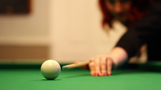 Woman Takes Shot During Pool / Billiards Game