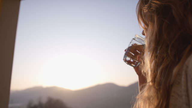 woman takes sip of fresh water from glass gar at sunset - drinking stock videos & royalty-free footage