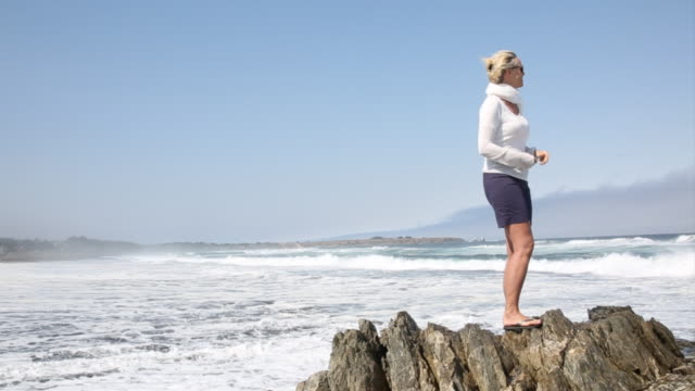 Woman takes smart phone pic of surf crashing on windy day