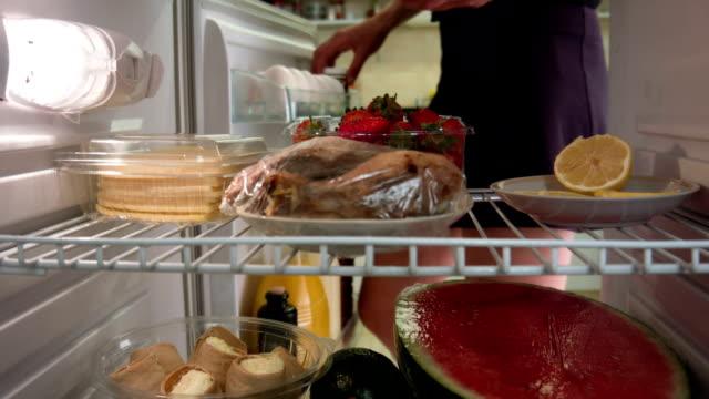 Frau nimmt tomatos aus dem Kühlschrank.