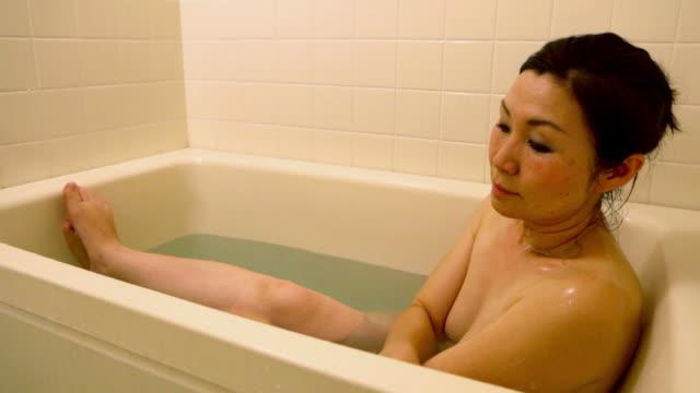 ms woman taking a bath at home / tokyo, japan - 風呂点の映像素材/bロール