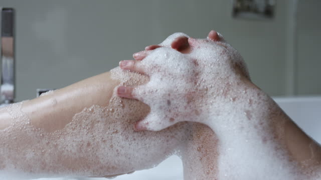 woman taking a bubble bath showing her legs and feet out of the water - vasca da bagno video stock e b–roll