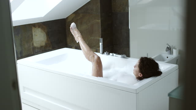 woman taking a bubble bath showing her legs and feet out of the water - bubble bath stock videos & royalty-free footage