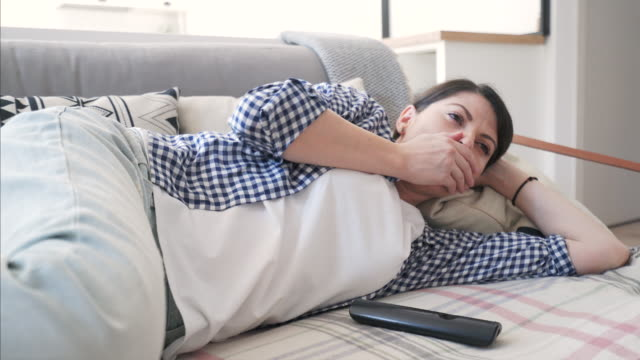 woman taking a nap while watching tv. - laziness stock videos and b-roll footage