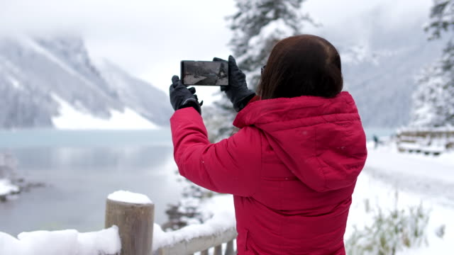 woman taking a photo of  winter lake louise - photographer stock videos & royalty-free footage