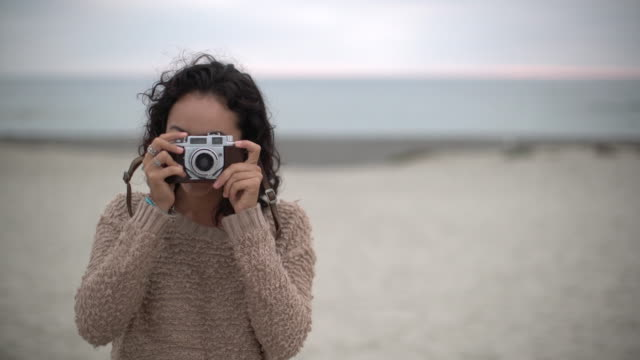 cu woman taking a photo with a retro camera on the beach. - junge frau allein stock-videos und b-roll-filmmaterial